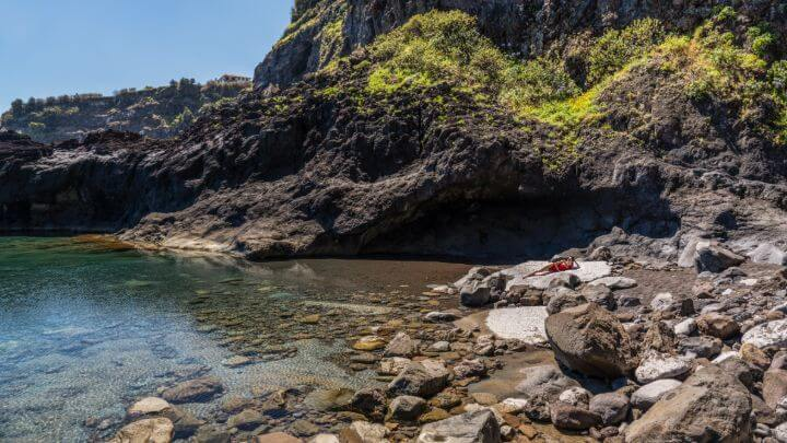 Madeira rocky cove with a mountain-backdrop by Henrique Seruca